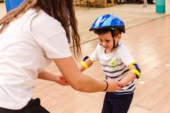 A child learns to roller skate, hand in hand. Indoors royalty free stock photography