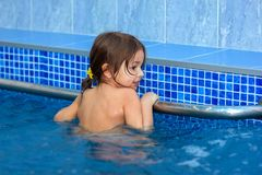The child learns to swim in the pool. And holds on to the banister Royalty Free Stock Photography