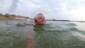 The Child Learns to Swim in the River. Close-up stock video footage