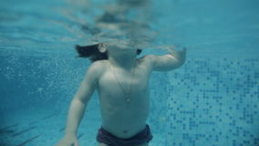The child learns to swim underwater in the pool stock footage