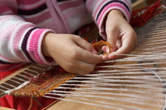 Child learns to weave Stock Image
