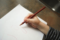 The child learns to write. Child's hand holding a red pencil on a white sheet of paper. The child learns to write royalty free stock photo