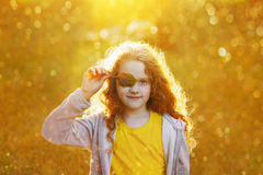 Child with leaves eyes, resting in golden autumn park. Royalty Free Stock Photos