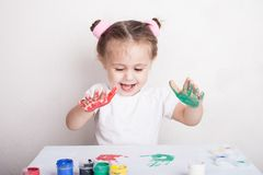 The child leaves her handprints on paper. Cute little girl royalty free stock photo