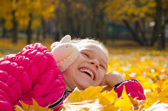 Child on leaves. Laughing child enjoying herself while lying on autumnal ground Stock Image