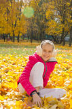 Child on leaves. Smiling child sitting on yellow autumn leaves Stock Image