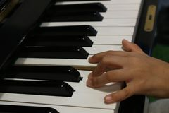 Child left hand playing piano royalty free stock photo