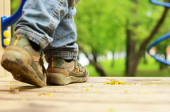Child legs in jeans and shoes at playground Stock Photo