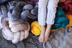 Child legs in pajamas next to unusual pillows royalty free stock photo