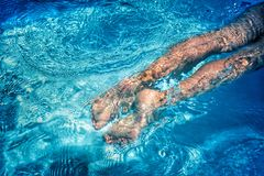 Child legs swimming in pool Stock Photos
