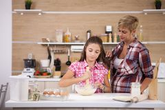 Child leping mother prepare delicious food for both of them. Happy family stock images