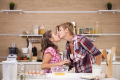Child leping mother prepare delicious food for both of them. Happy family royalty free stock photography