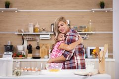 Child leping mother prepare delicious food for both of them. Happy family stock photos