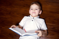 Child Lesson. Little boy doing homework on the wooden floor Stock Photo