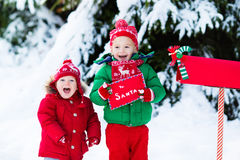 Child with letter to Santa at Christmas mail box in snow. Happy children in knitted reindeer hat and scarf holding letter to Santa with Christmas presents wish Royalty Free Stock Photo