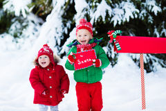 Child with letter to Santa at Christmas mail box in snow Stock Photos