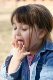 Child Licking Her Hand Royalty Free Stock Photo