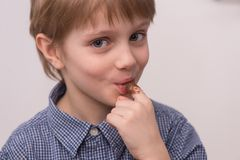 Child licks chocolate glaze with finger. Stock Photos