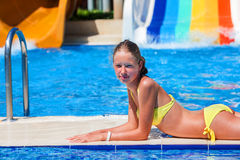 Child lie on edge of swimming pool and looking at camera. Stock Photo