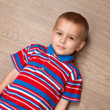Child lie on the floor Stock Images