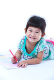 Child lie on the floor drawing on paper and smiling.  On white Royalty Free Stock Photography