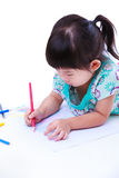 Child lie on the floor and drawing on paper. On white. Royalty Free Stock Photo