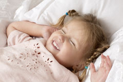 The child lies on a bed. Portrait of a smiling girl with pigtails Stock Images