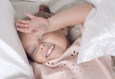 The child lies on a bed. Portrait of a smiling girl with pigtails Royalty Free Stock Images