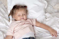 The child lies on a bed. Portrait of a smiling girl with pigtails Royalty Free Stock Photography