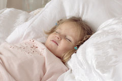 The child lies on a bed. Portrait of a smiling girl with pigtails Stock Photos