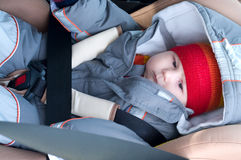 Child lies in car seat. The child is lying in the safety seat on forward of the car Stock Photo