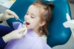 Child lies in dentist chair and doctor does checkup. Child lies with open mouth and napkin on chest in comfortable dentist chair and doctor in sterile rubber stock images