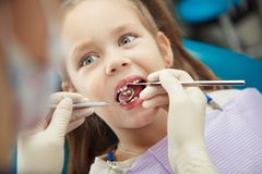 Child lies in dentist chair and goes through procedure Royalty Free Stock Photography