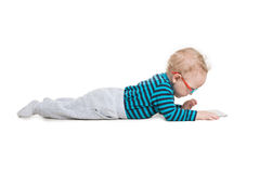 The child lies on the floor with glasses and looks at computer. The child lies on the floor with glasses Royalty Free Stock Image