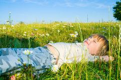 Child lies on the grass Royalty Free Stock Photos