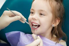 Child lies in dentist chair and doctor does checkup. Child lies with open mouth and napkin on chest in comfortable dentist chair and doctor in sterile rubber royalty free stock image