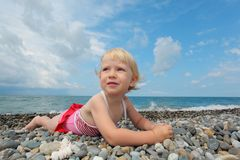 Child lies on pebble beach Royalty Free Stock Photography