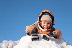 Child lies on snow hill Royalty Free Stock Photography