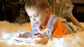 The child lies on a soft white blanket in the children`s room. He is watching cartoons on the smartphone. Christmas. Happy childhood. The child lies on a soft royalty free stock photography