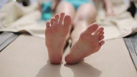 Child lies on a sun lounger by the pool at the hotel and moves her feet stock footage