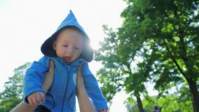 Child life, happy cute infant in blue hood plays in air in vivid sunlight stock footage