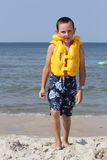 Child with life jacket. Six  years old  boy wearing in life jacket and learning to swim in the sea Royalty Free Stock Image