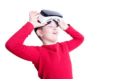 Child lifts up virtual reality headset to see. Smiling boy in red long sleeve shirt lifting his virtual reality headset over eyes to see something in front of Stock Photos