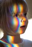 Child with light on her face. A portrait of a young girl with a colorful light pattern on her face Stock Image