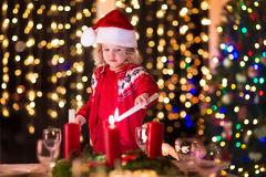 Child lighting a candle at Christmas dinner Stock Images