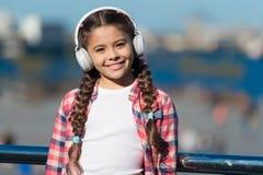 Child listen music outdoors modern headphones. Kid little girl listen song headphones. Music account playlist. Customize stock photography