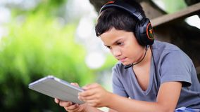 Child listen music and playing on the computer with headphones outdoor stock footage