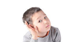 A child boy is listening to something, holding his hand around his right ear. Isolated on white background Royalty Free Stock Photography