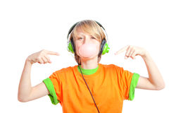 Child listening music. Child blowing gum and listening to music with headphones Royalty Free Stock Images