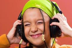 Child listening music in headphones Stock Photos